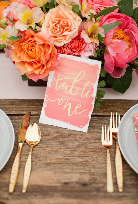 Pink watercolor table number with gold writing