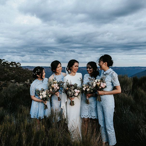 The bridesmaids are wearing all blue in mismatched lace styles.