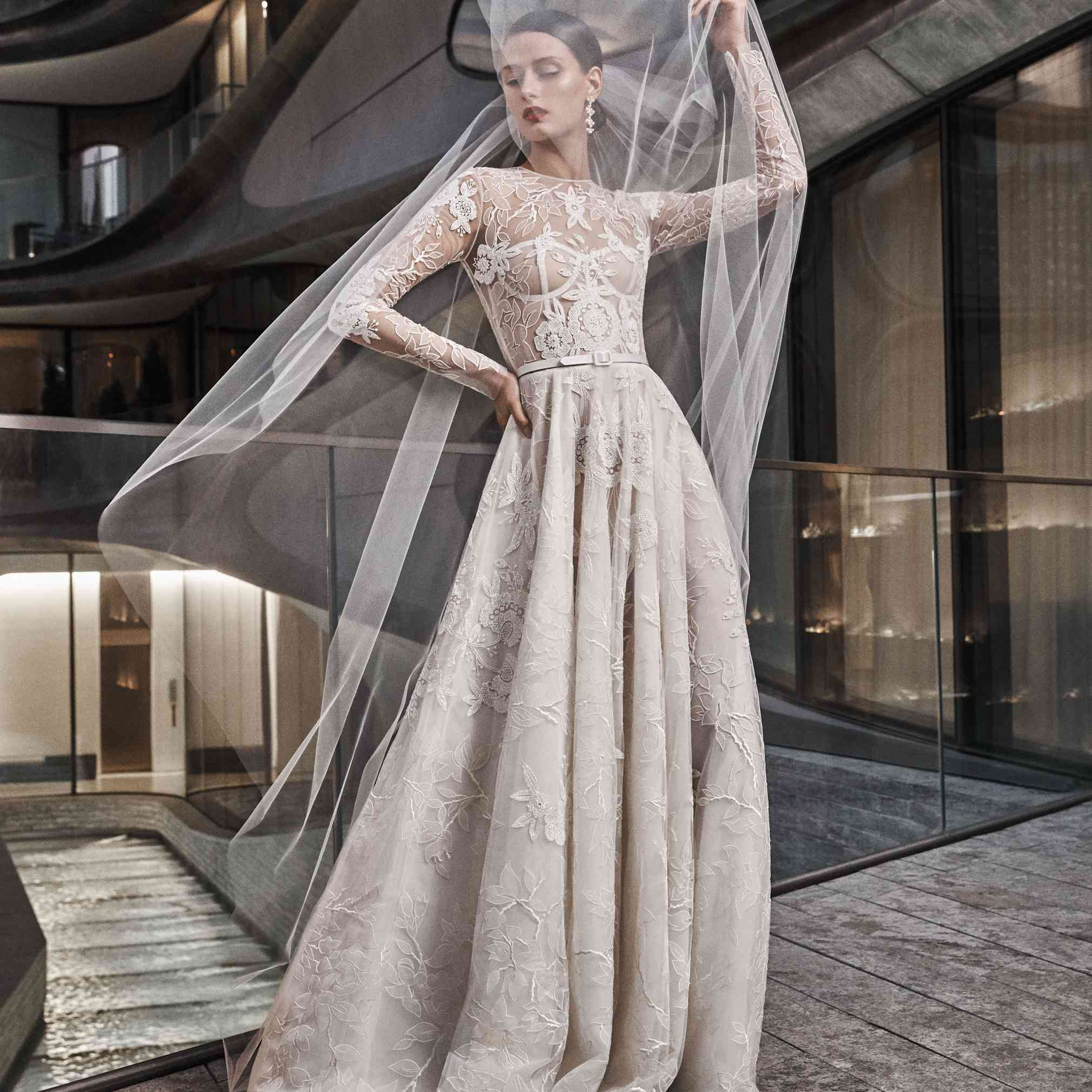 Model in long-sleeve A-line gown with floral and bead details