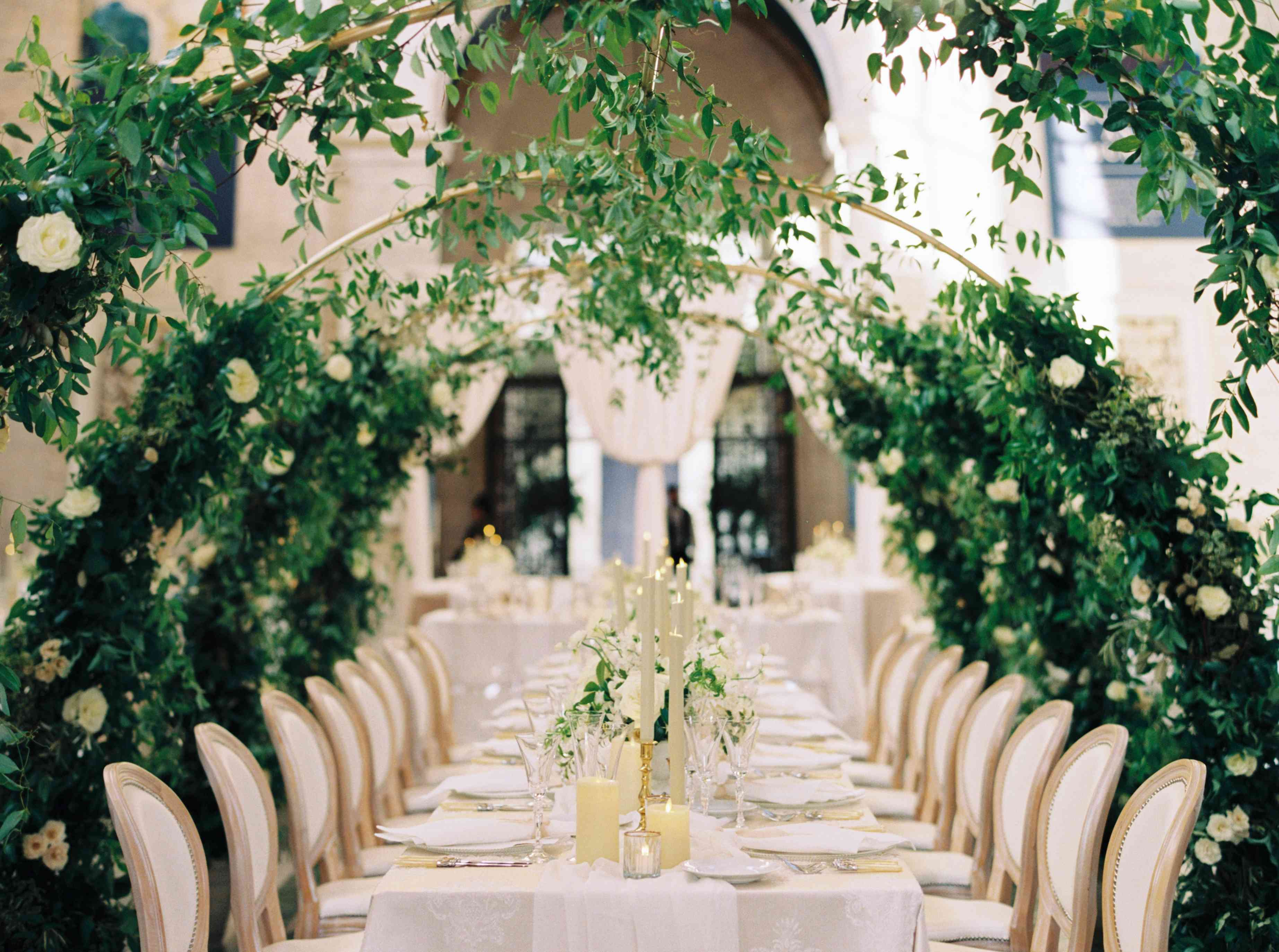 Greenery arches over reception tables