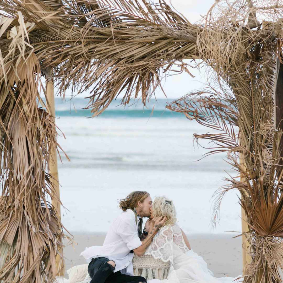 Newlyweds kissing under arbor made entirely of dried palm leaves