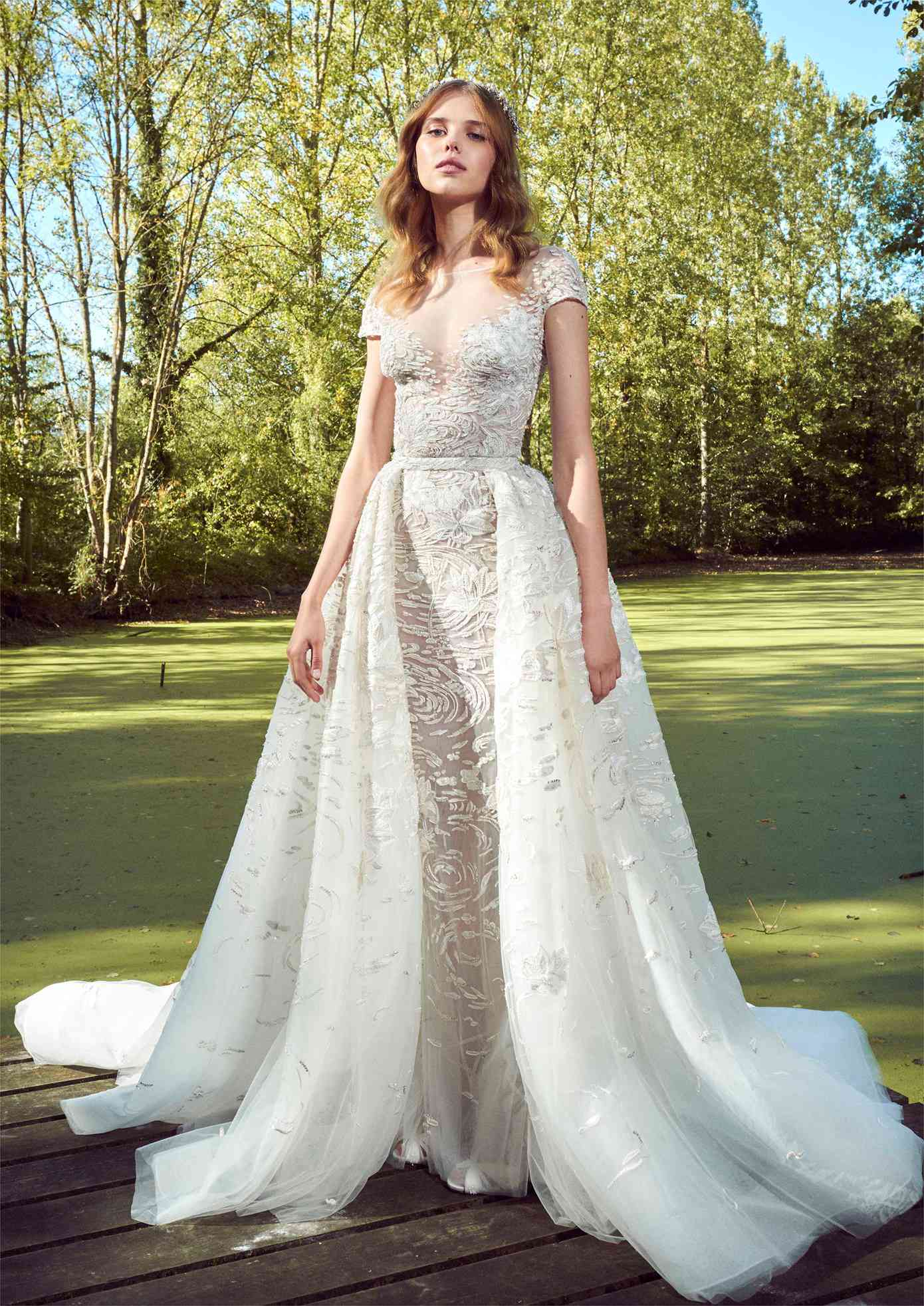 Model in a tulle sheath gown with cap sleeves, an illusion neckline, 3D beaded embroidery and a voluminous embroidered tulle overskirt