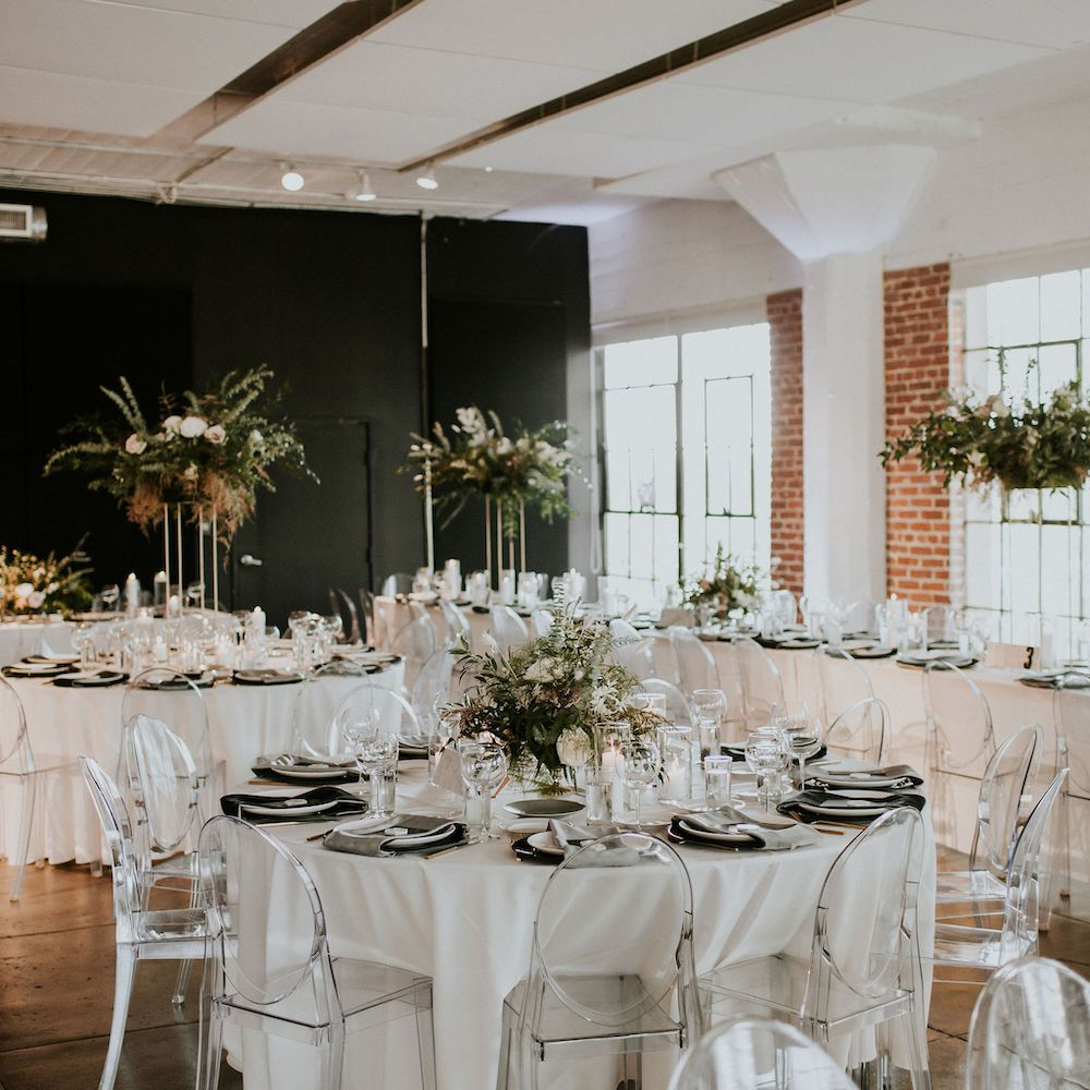 Wedding reception with acrylic ghost chairs seated at round tables