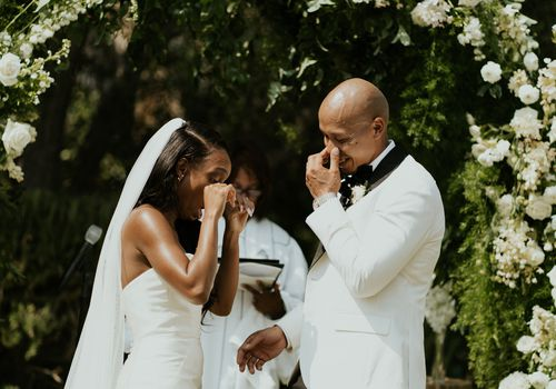 Bride and groom crying at the altar