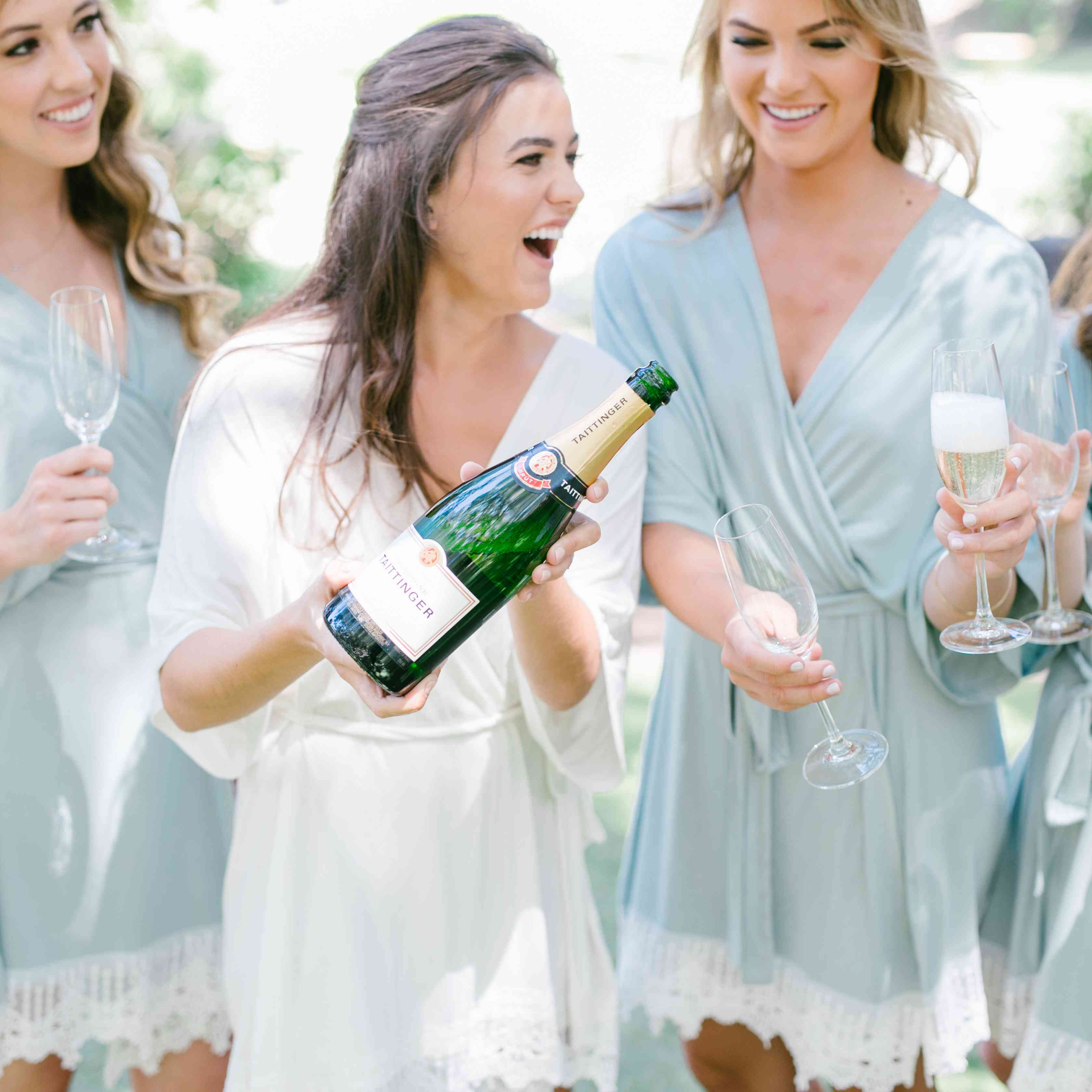 bride and bridesmaids getting ready with champagne