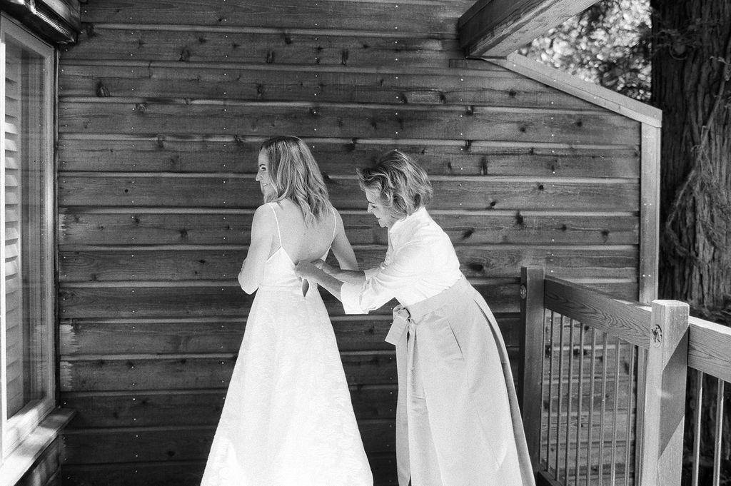 mother zipping bride's dress