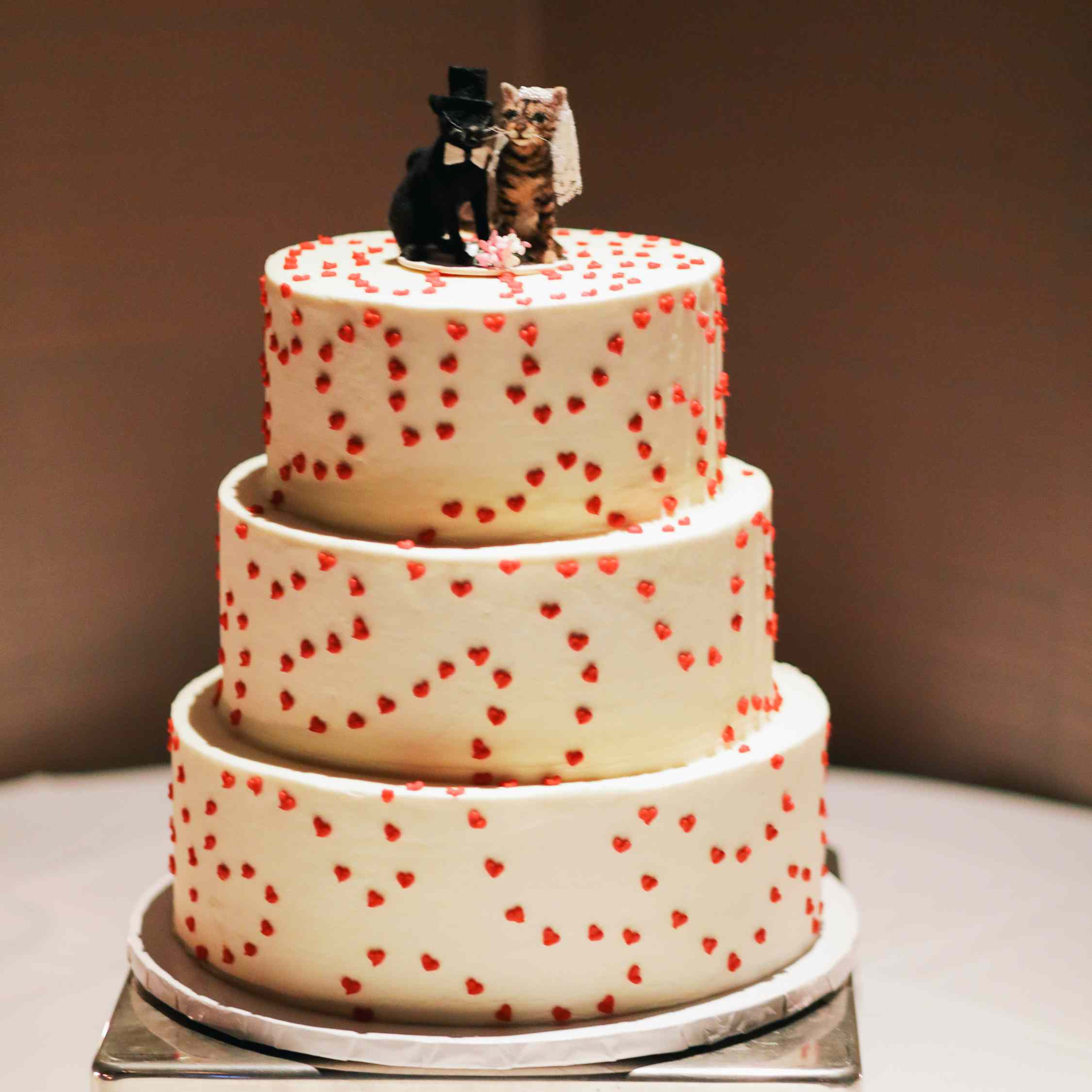 Three-tiered white wedding cake with tiny red fondant hearts and cat cake toppers
