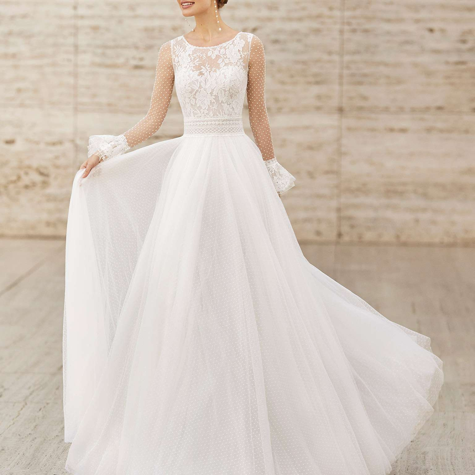 Model in wedding gown with illusion neckline and sleeves