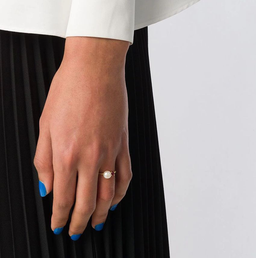 Hand with blue nail polish and pearl ring