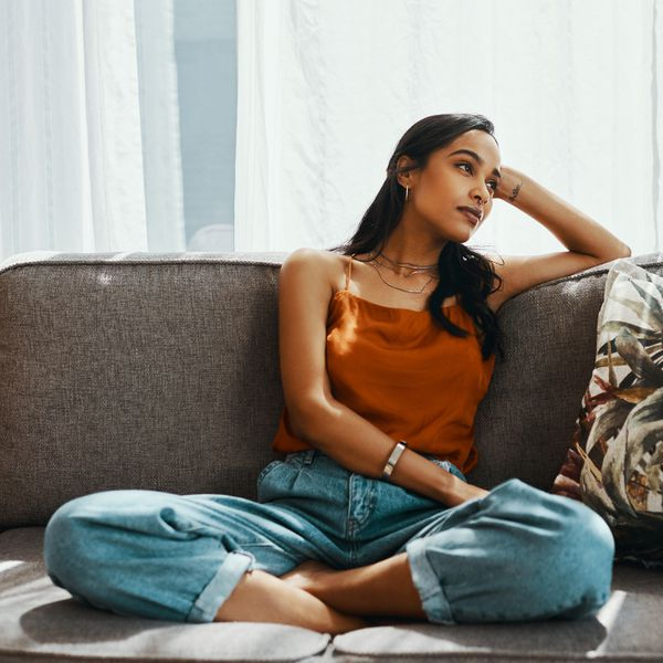 Woman sitting crisscross on a couch leaning on her hand and daydreaming