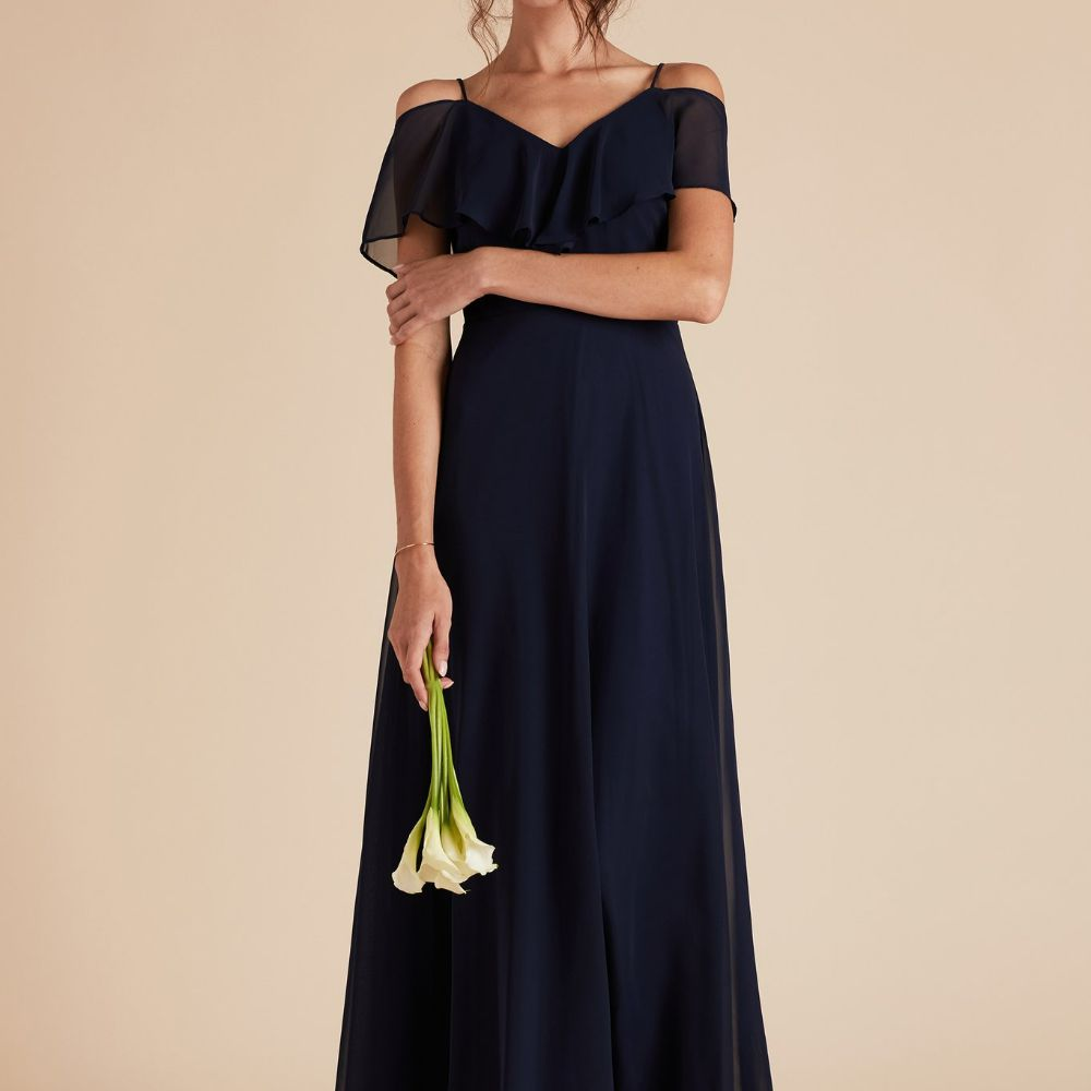 Model in a navy blue ruffle paneled off-shoulder gown