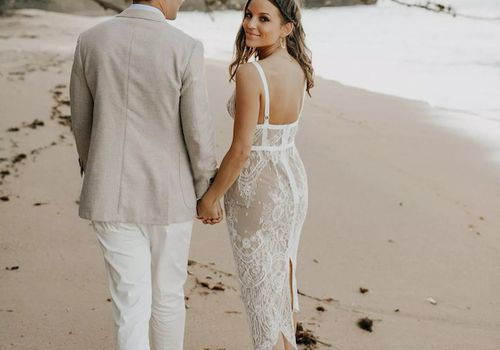 Bride wearing a white lace dress walks on the beach with groom