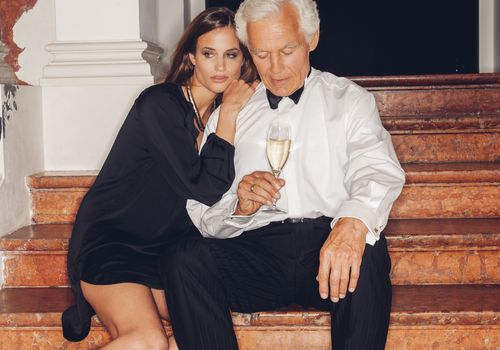 A younger woman and an older man sitting on steps.
