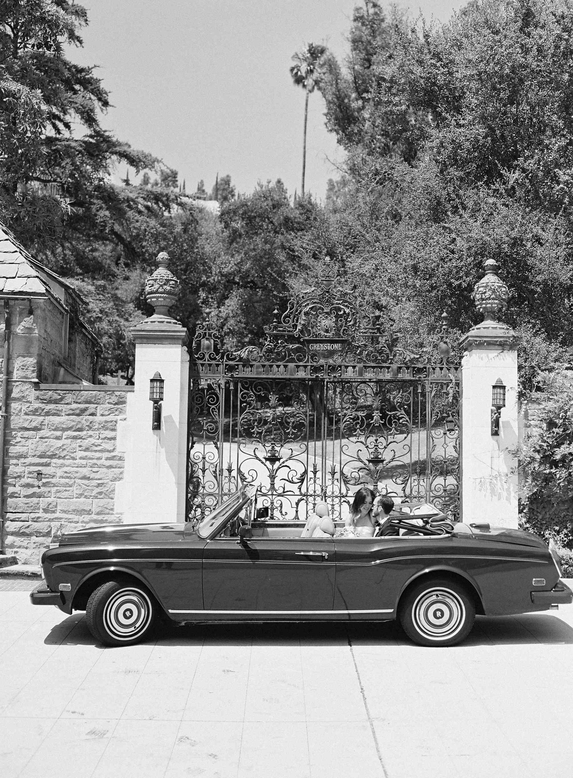 The couple poses in a vintage Rolls Royce
