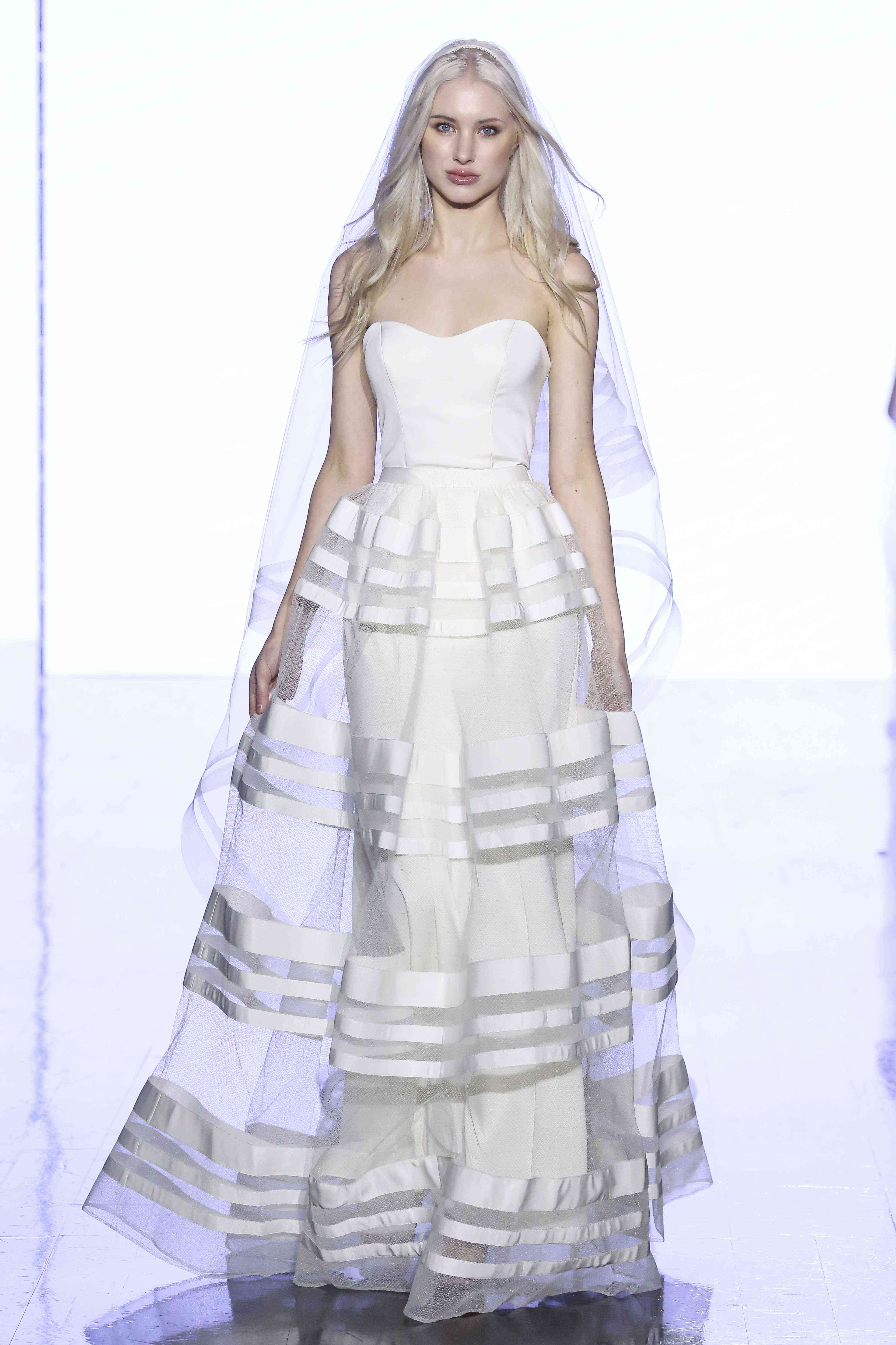 Model in strapless sheath dress with a satin-striped mesh overskirt