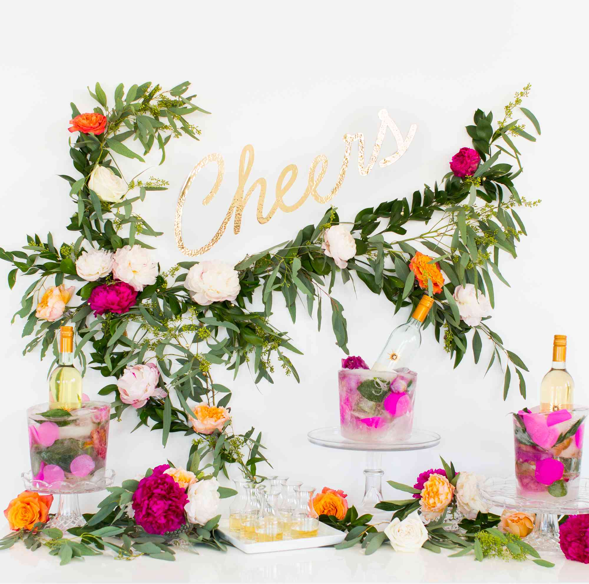 A bar setup with floral décor and bottles of wine in flower filled ice buckets