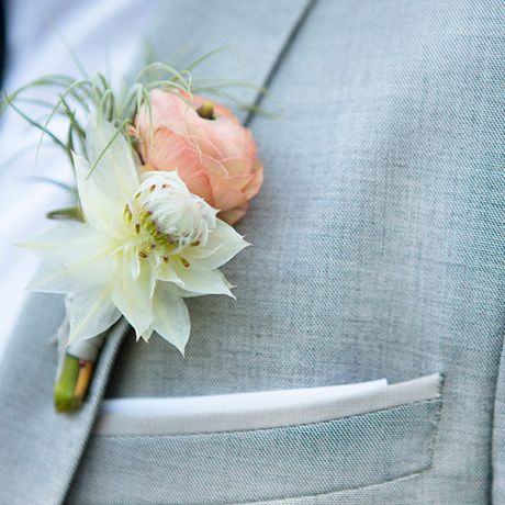 An air plant and peach ranunculus boutonniere created by The Little Branch
