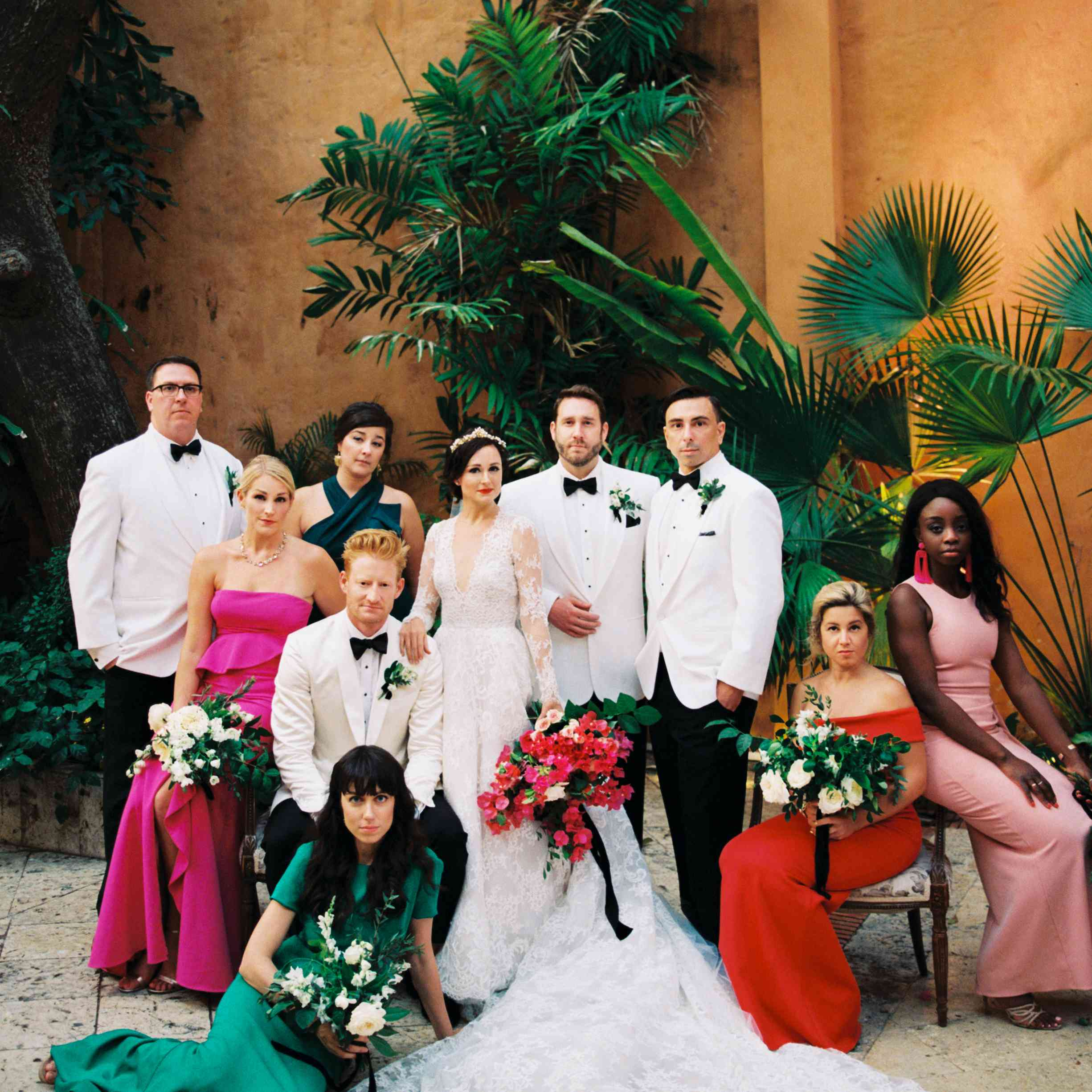 Groomsmen in white tuxedo jackets and bridesmaids in jewel-toned dresses