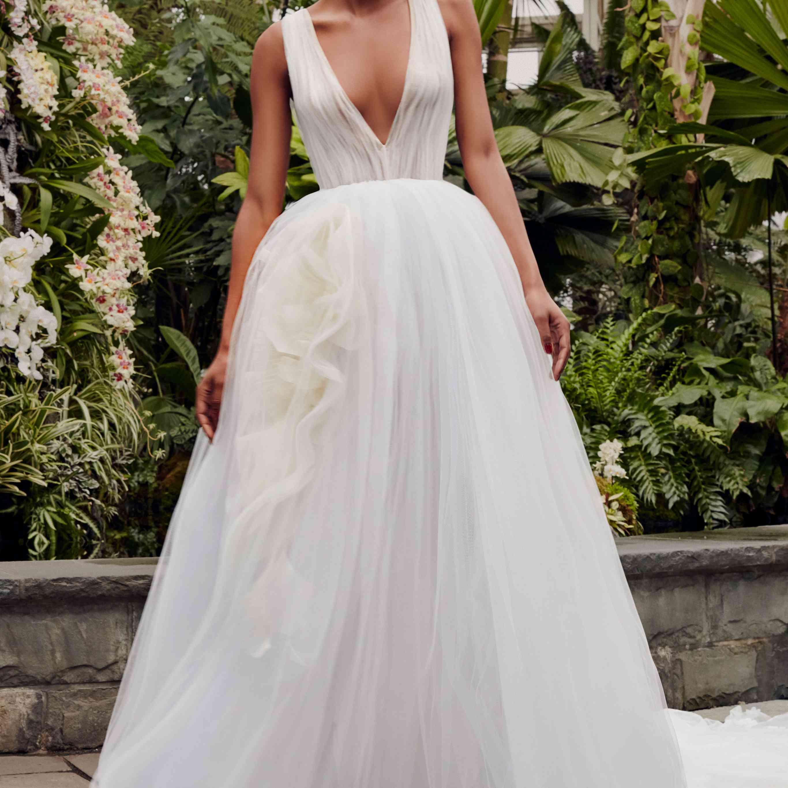 Model in V-neck white tulle ballgown