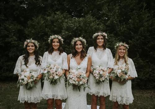 Bridesmaids wearing matching lace boho dresses.