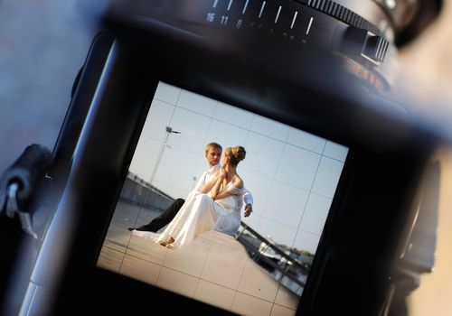 Photo of a camera displaying a photo of a couple on their wedding day