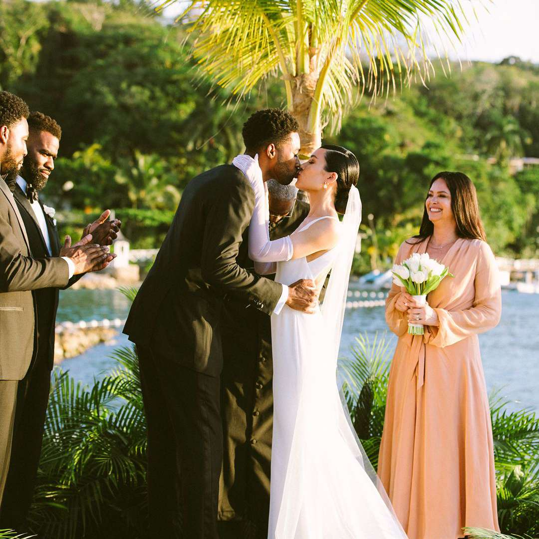 couple kissing under palm tree