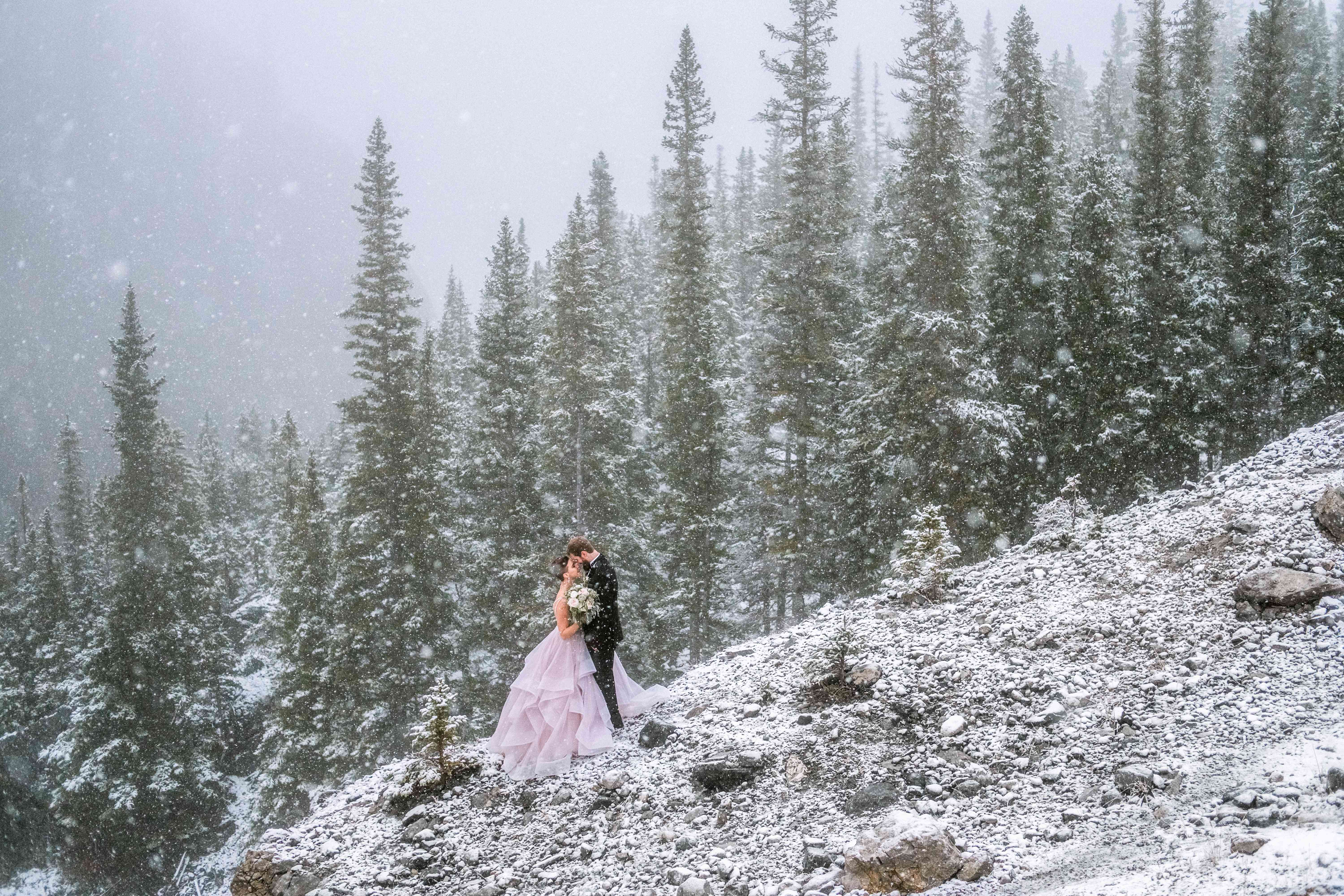 Bride and groom kissing mountainside in the snow with evergreen trees in the background