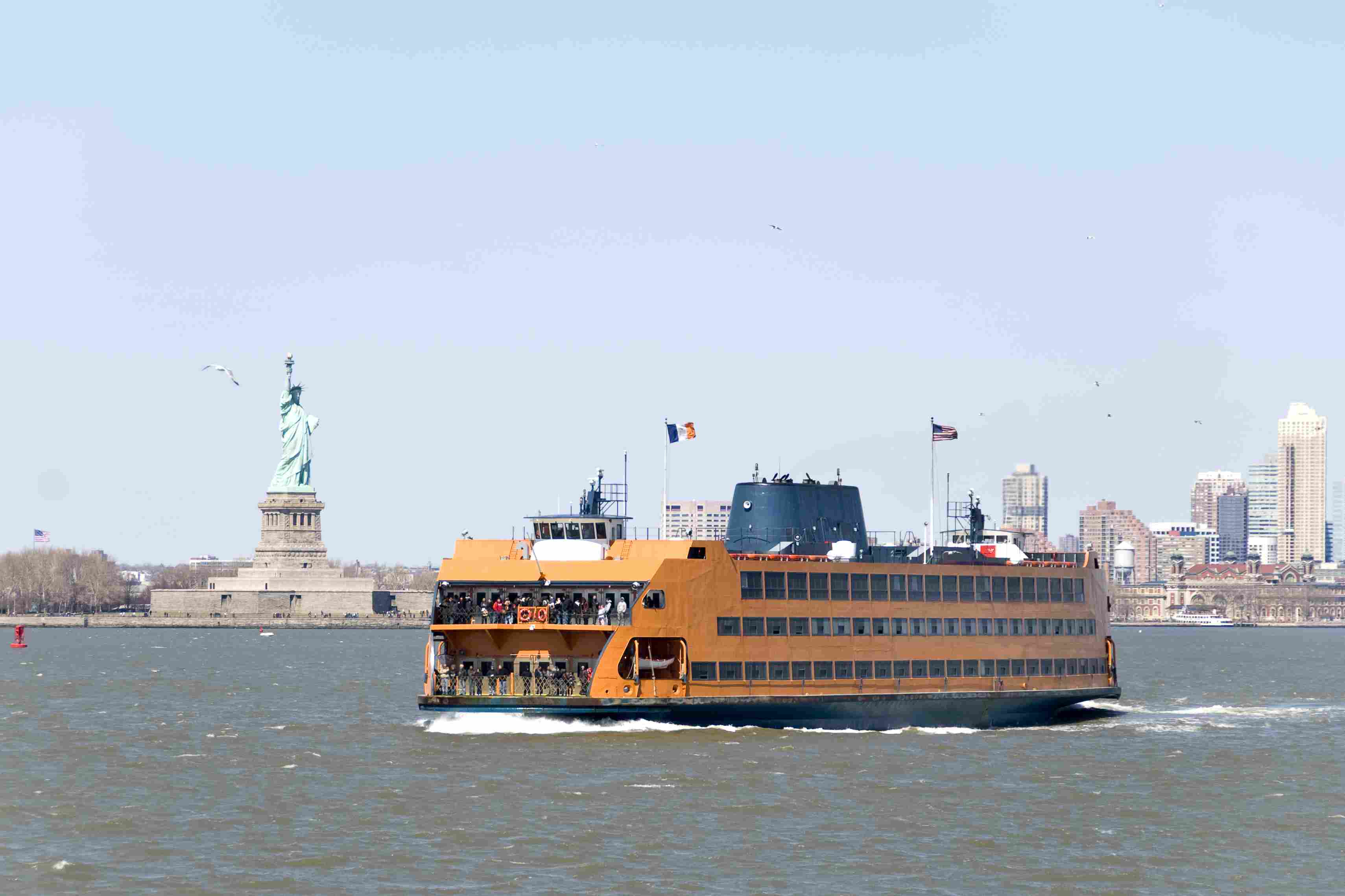 Staten Island ferry coming from Manhattan and passing by the Statue of Liberty
