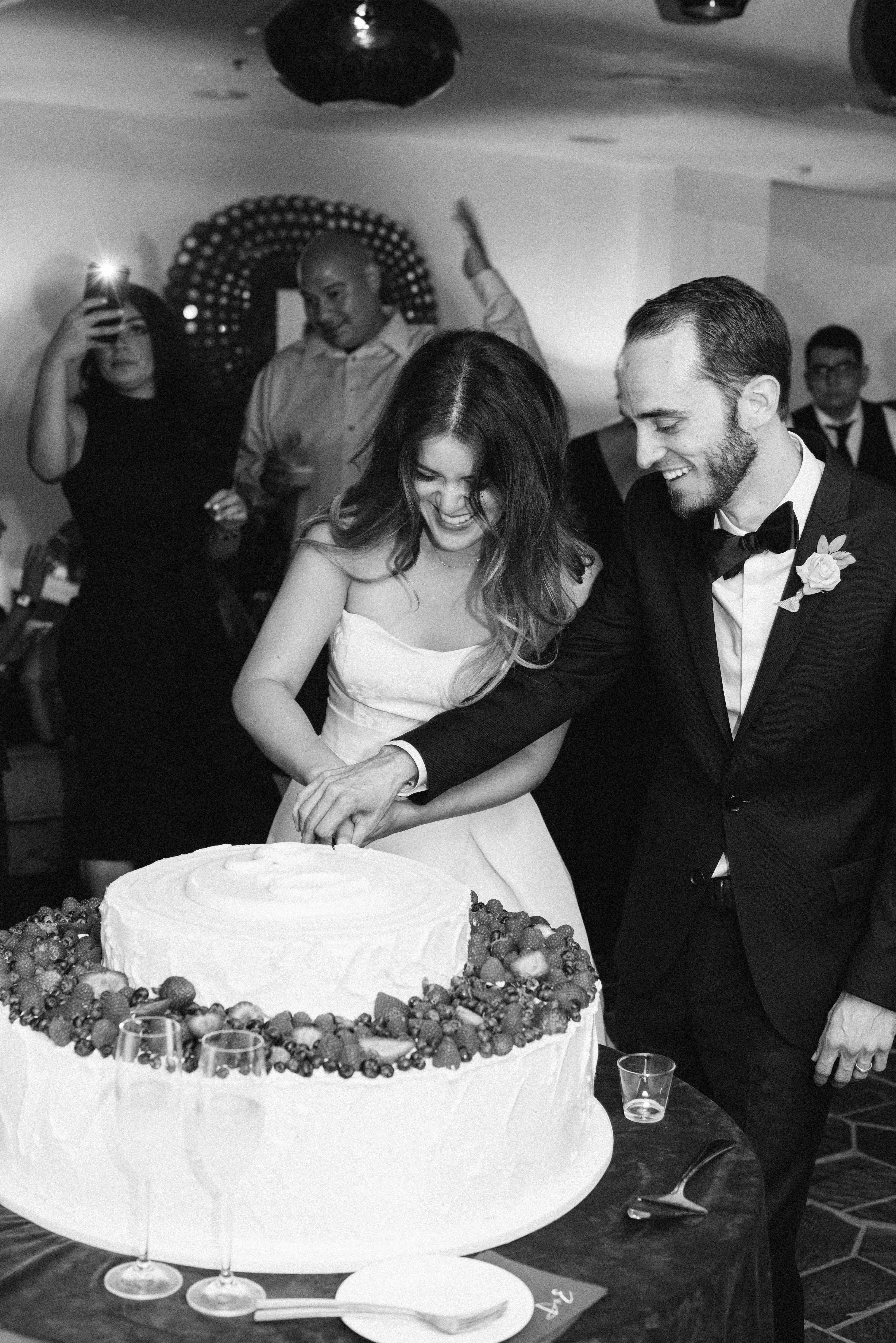 bride and groom cutitng cake