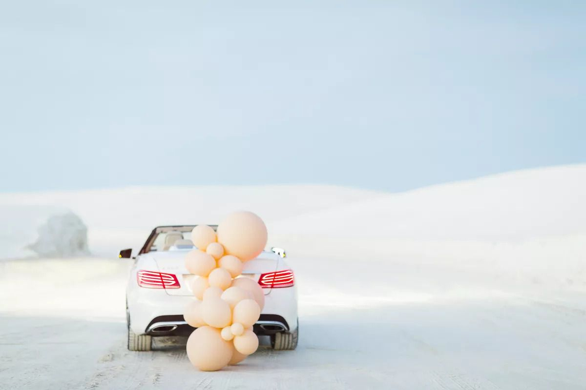 Peach-colored balloons attached to a getaway car