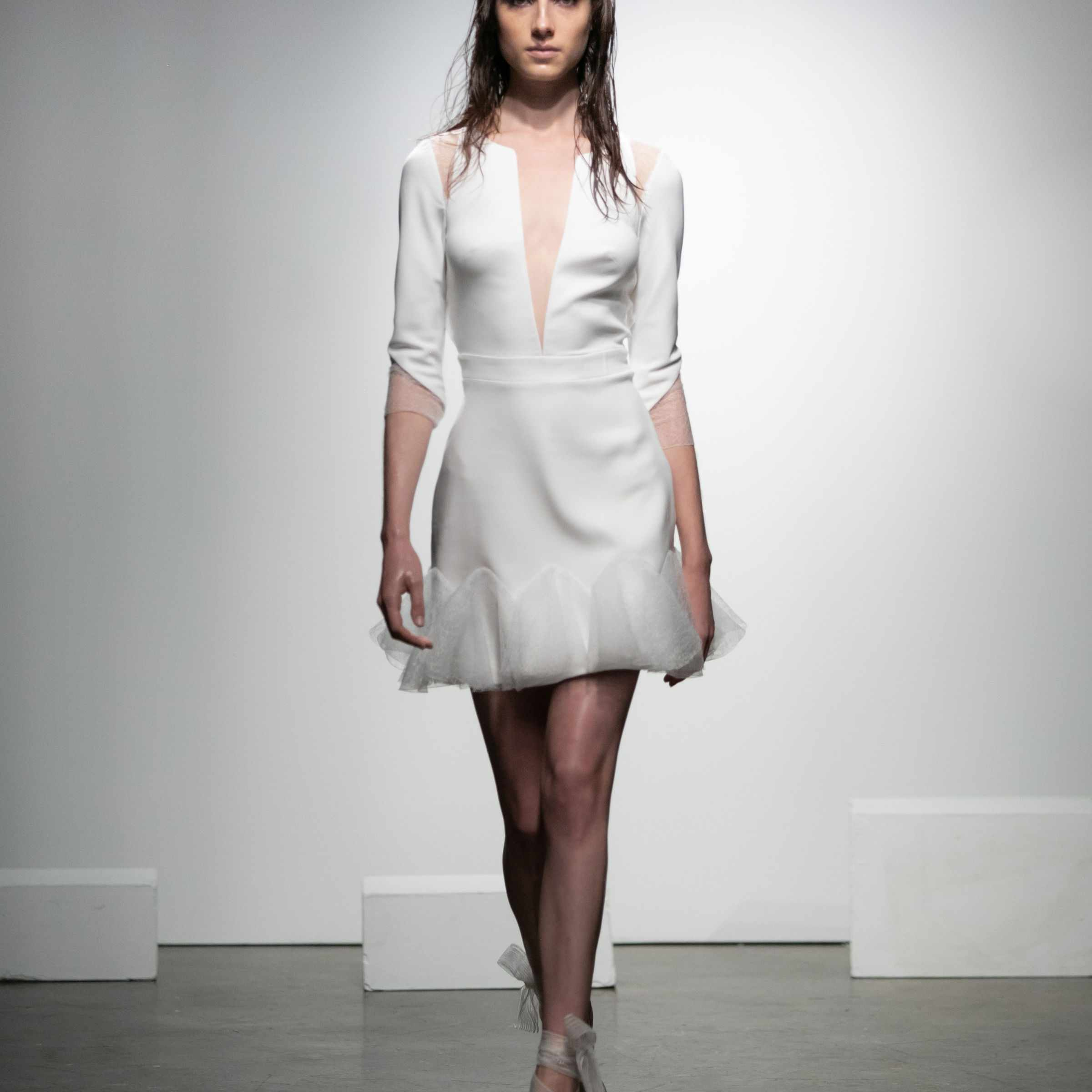 Model in three-quarter-sleeve mini dress in crepe with illusion plunging neckline and ruffles in fishnet tulle
