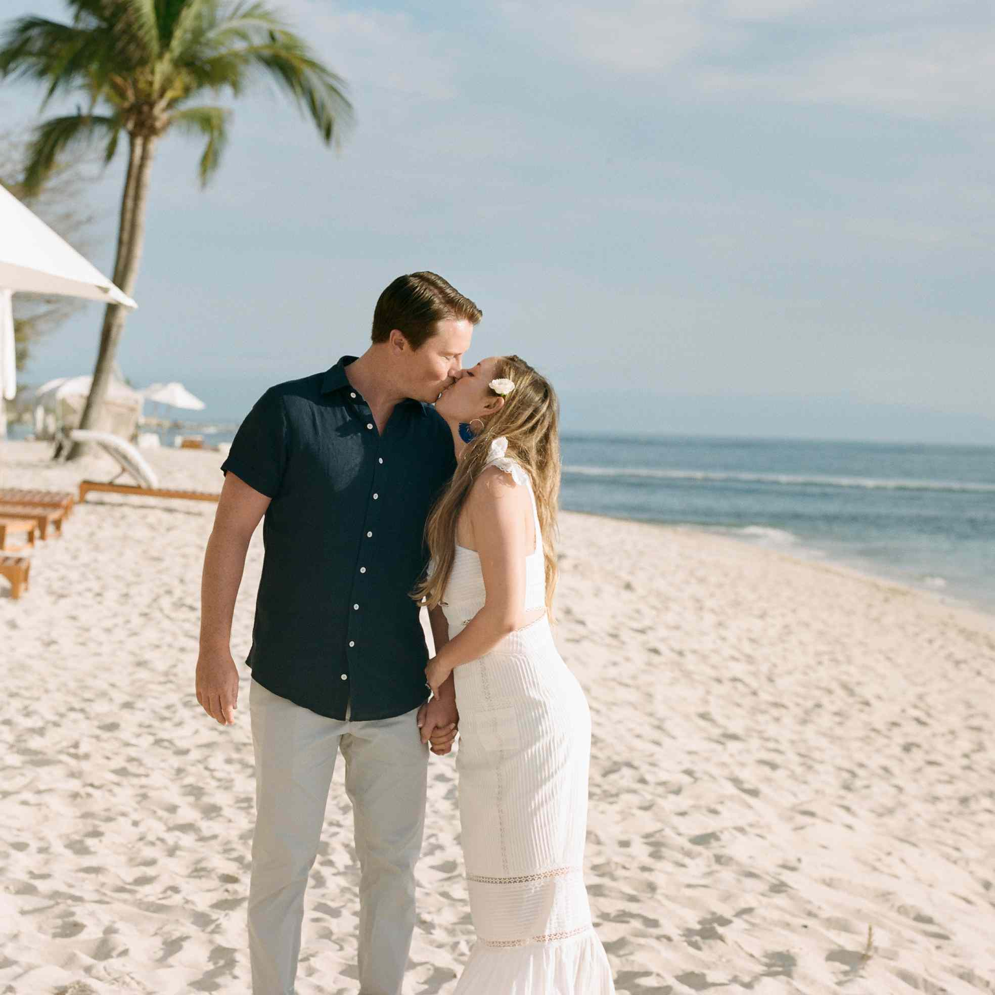 The bride and groom kiss on the beach