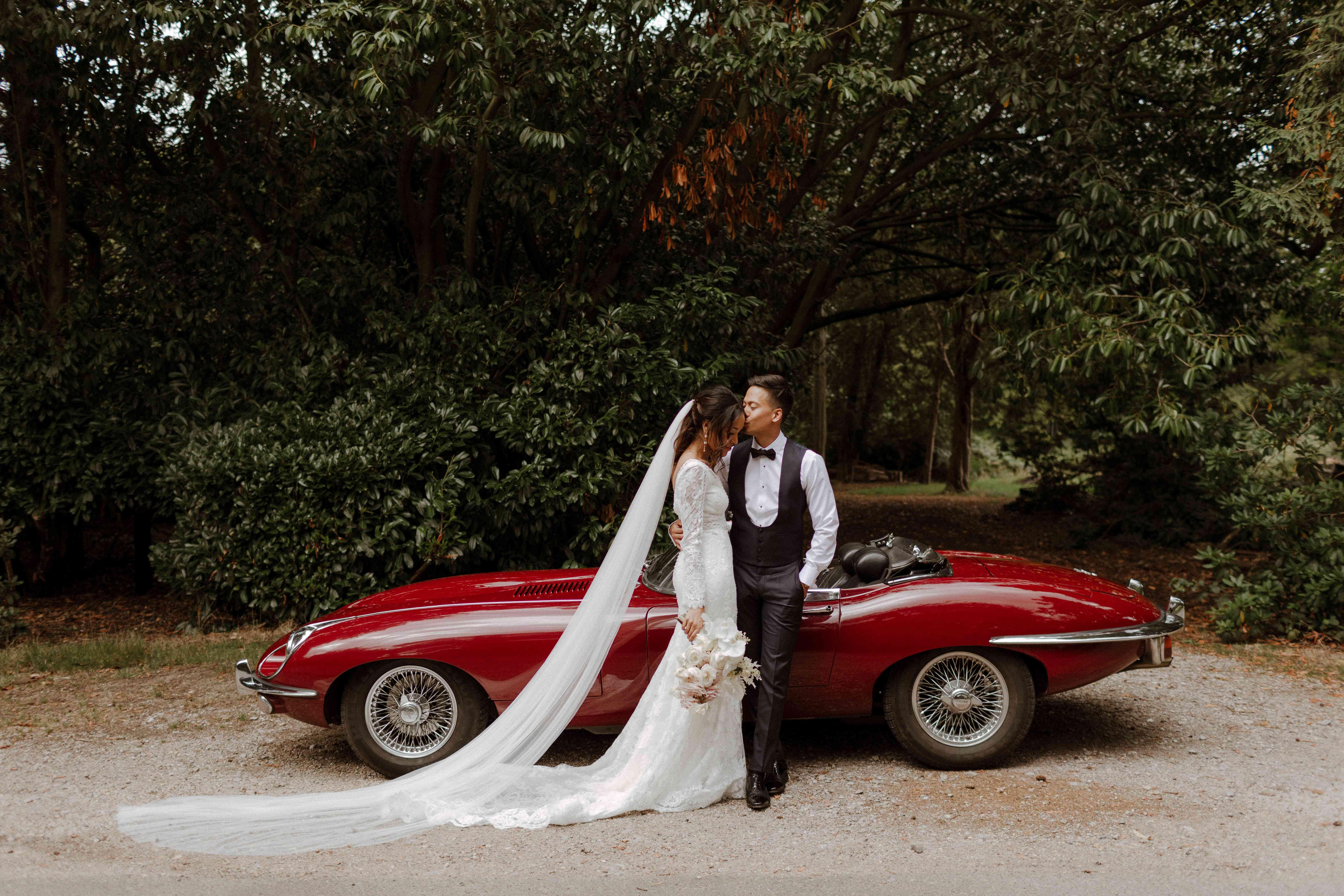 Couple kisses by red Jaguar