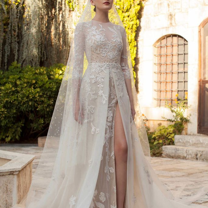 Model in long sleeve sheer dress with lace overlay and high slit skirt