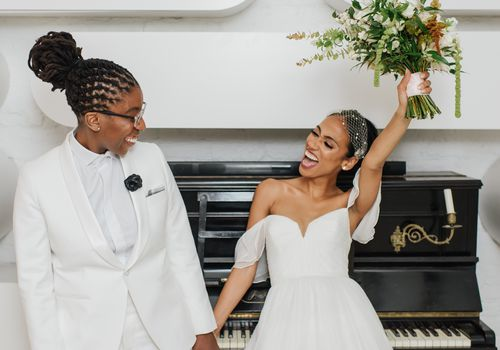 Two brides holding hands and posing in front of a piano, bride on the left holding up her bouquet and smiling
