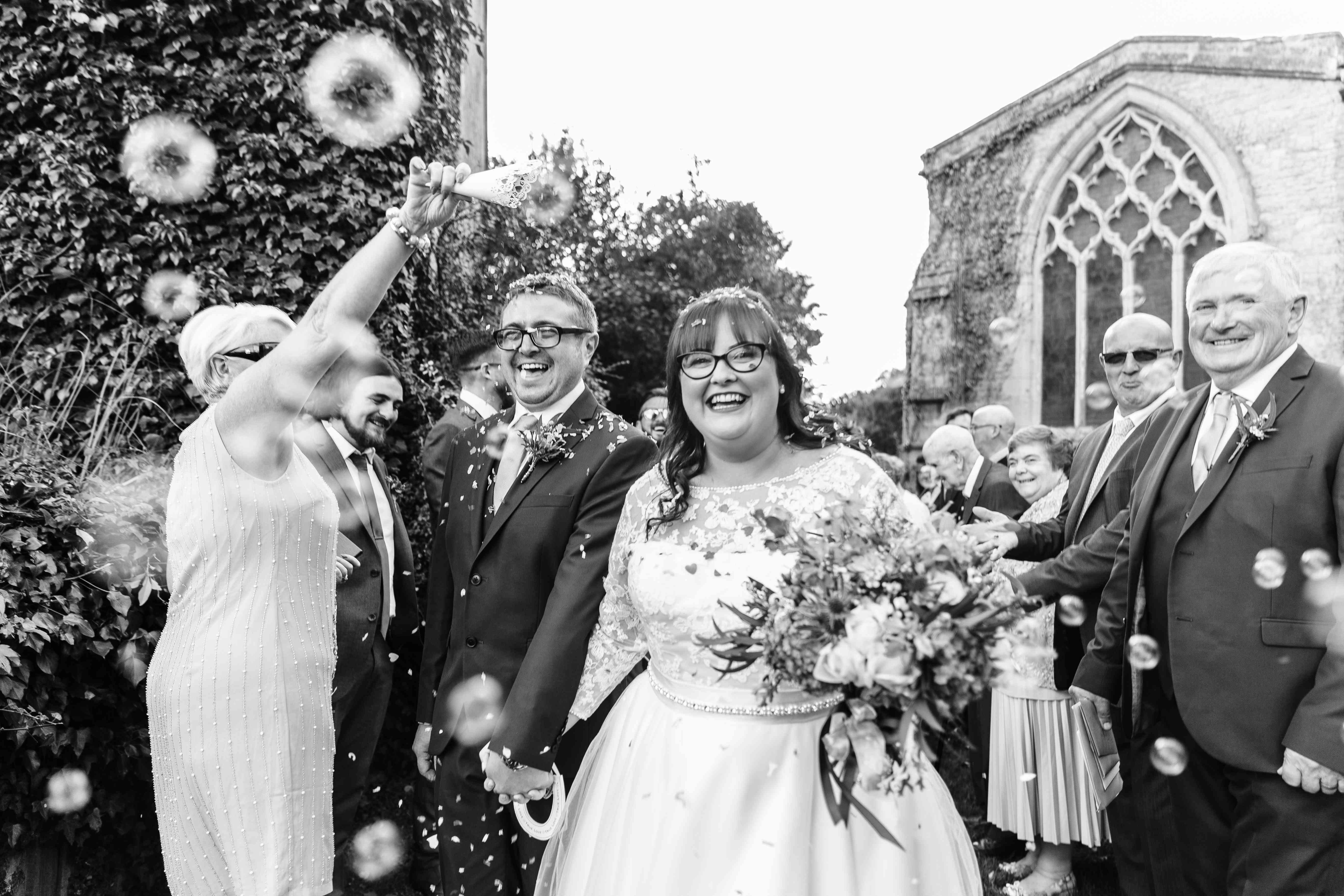Bride and groom exiting wedding while guests blow bubbles