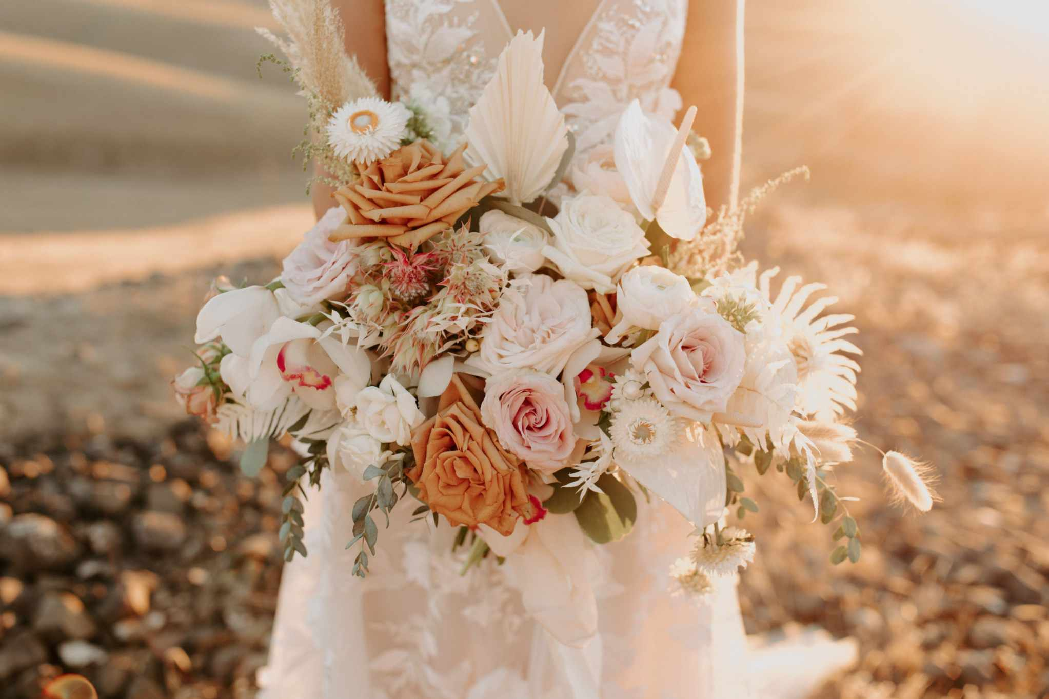 Bride holding bouquet of of white, pink and tan roses mixed with sprigs of greenery and pampas grass