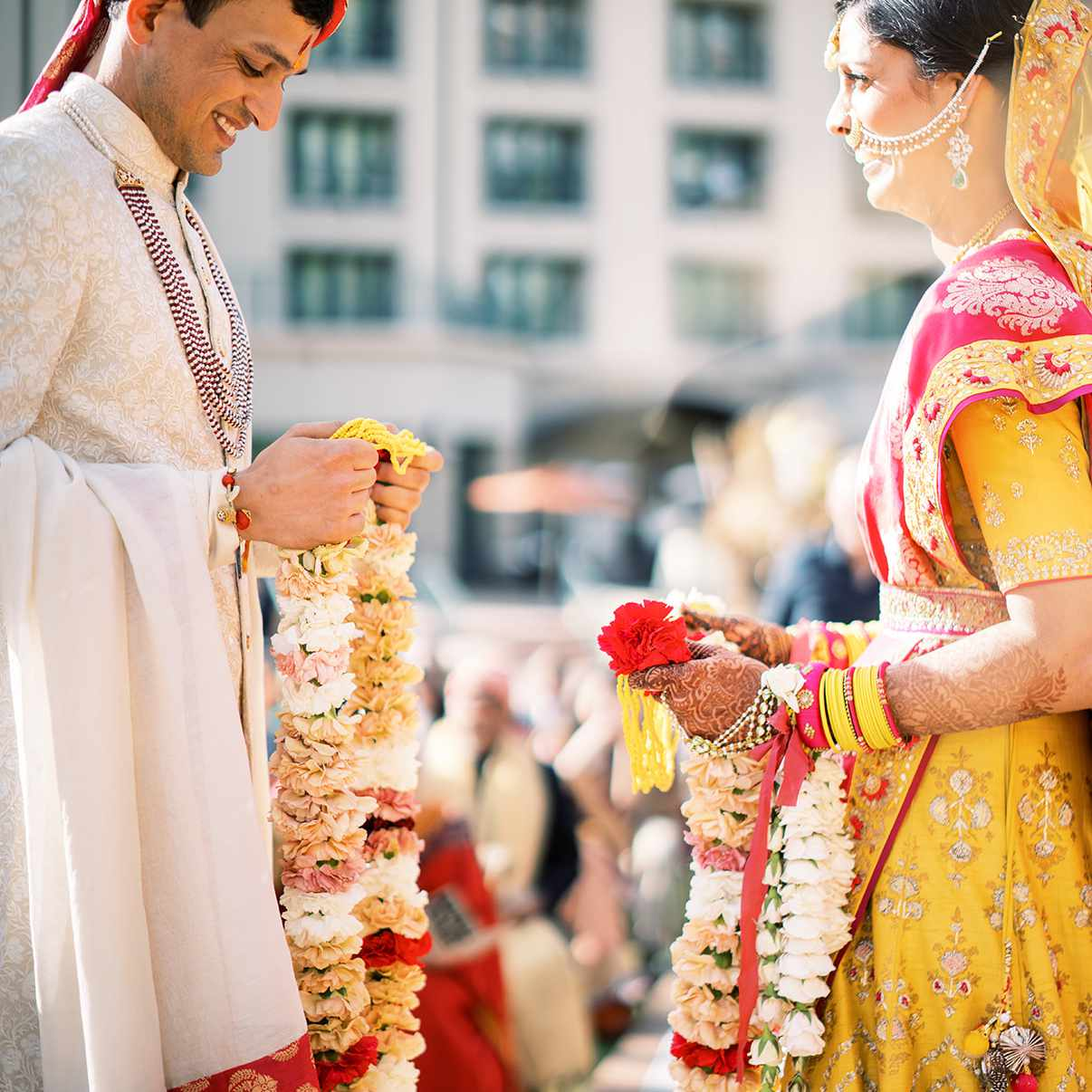 bride and groom exchanging floral garlands