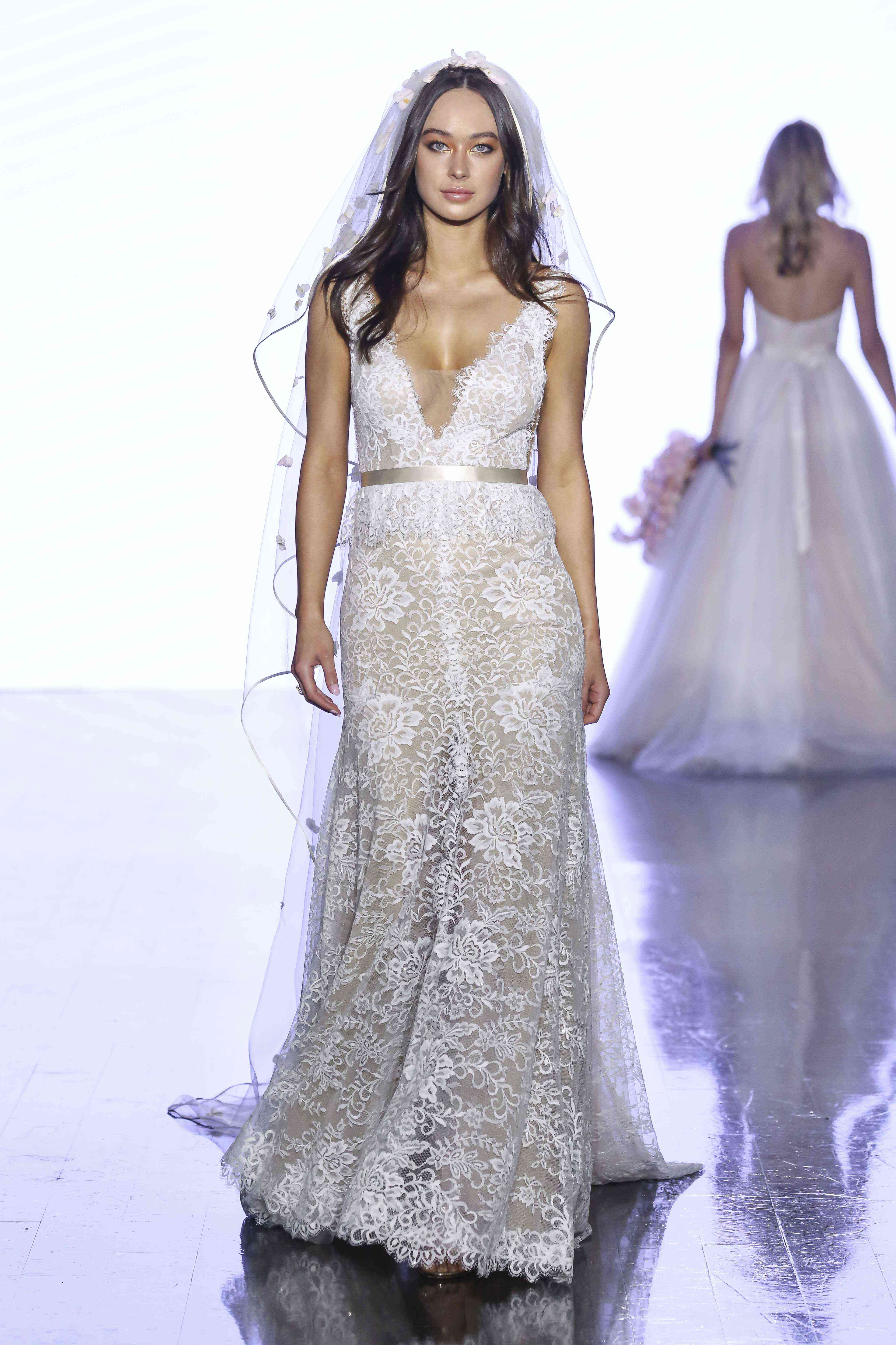 Model in sleeveless beaded lace column wedding gown with a plunging illusion neckline and satin ribbon belt