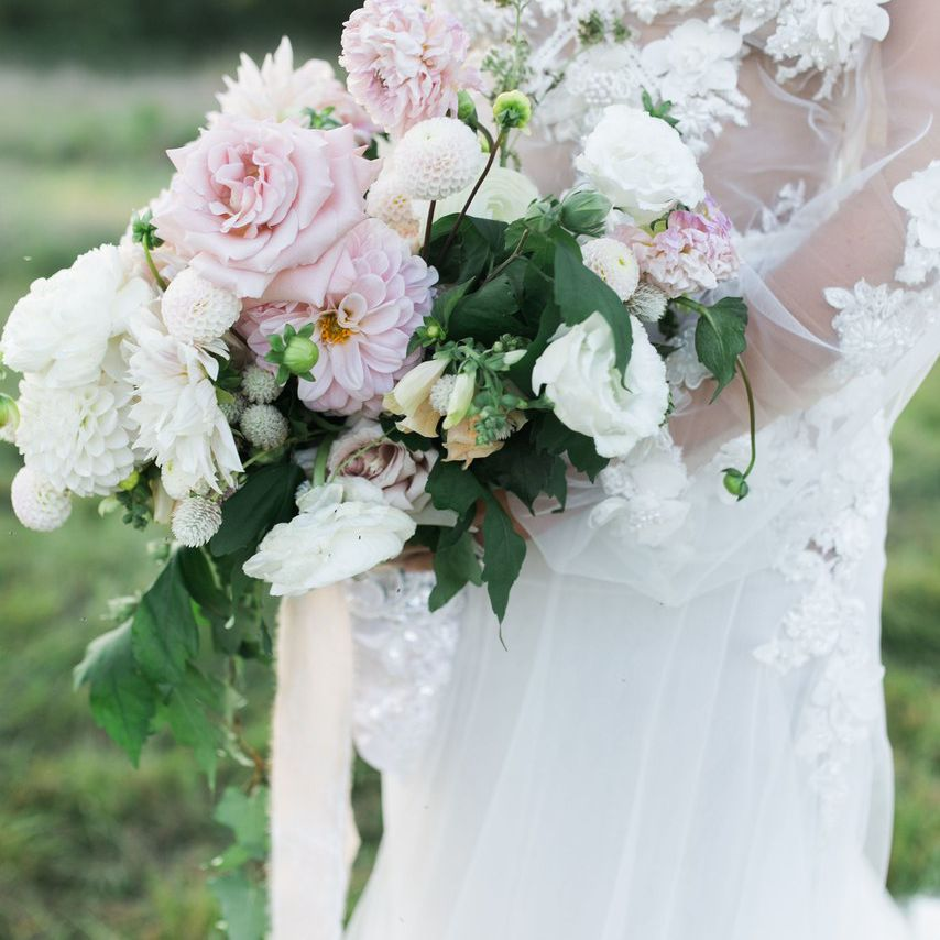 Bride holding a bouquet of pink and white roses, dahlias and peonies