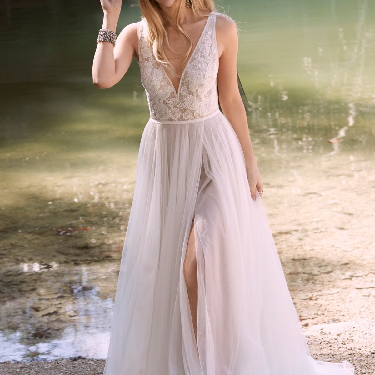 Model in V-neck gown with lace bodice and tulle skirt with front slit