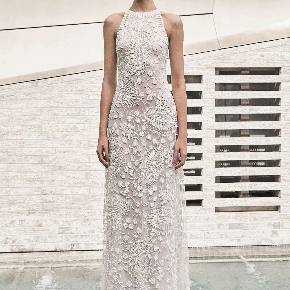Model in sleeveless embroidered gown