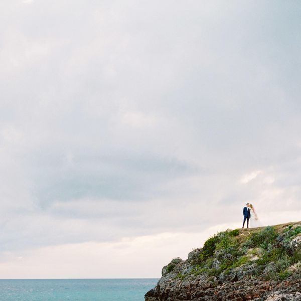 A couple on a cliff overlooking the water at the Cove, in Eleuthera