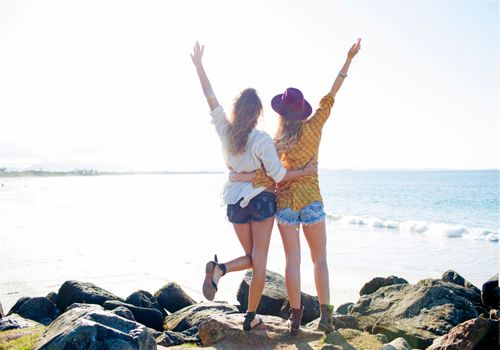 Two girls raising their arms by ocean