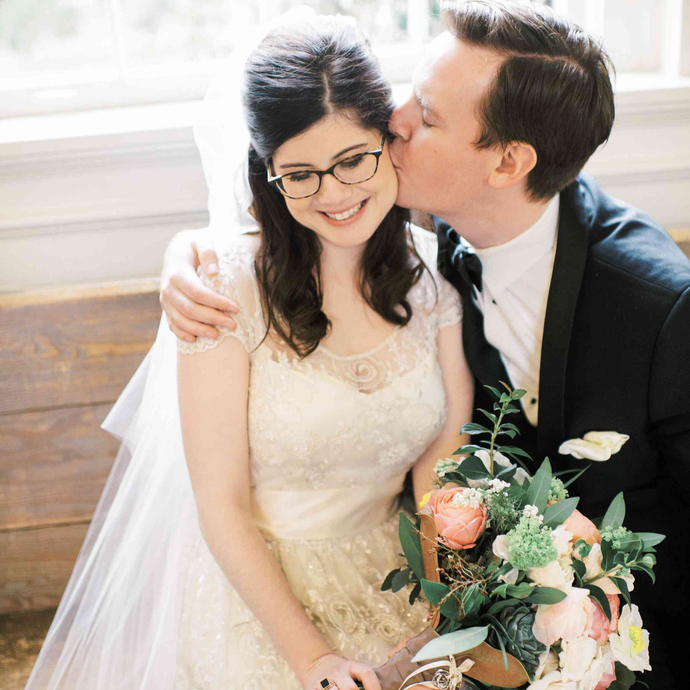 Groom kissing his bride on the cheek, who is wearing glasses and holding a bouquet