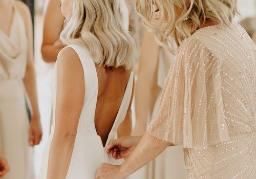 Mother zipping up daughter's wedding dress