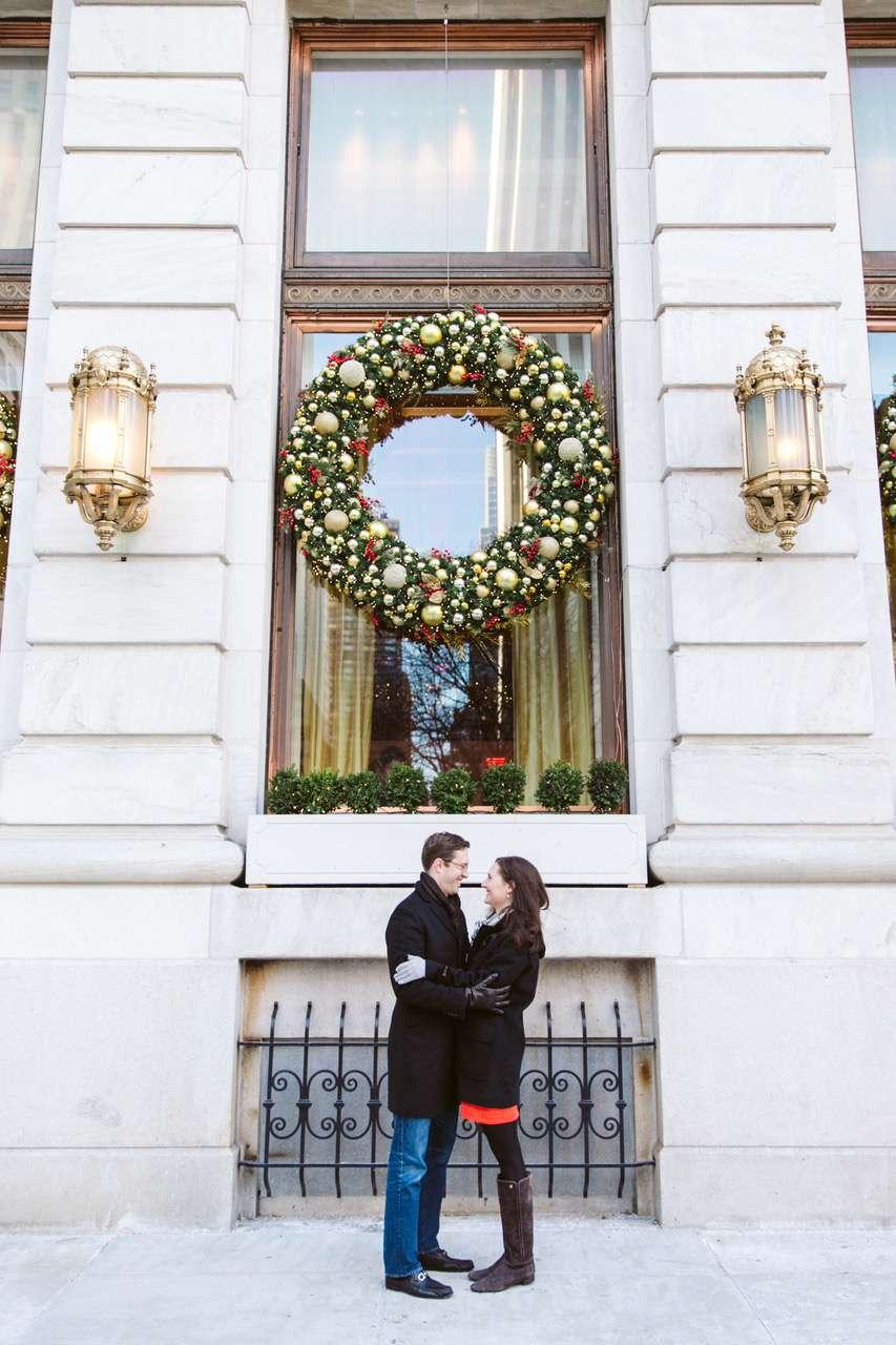 Couple posing under large wreath