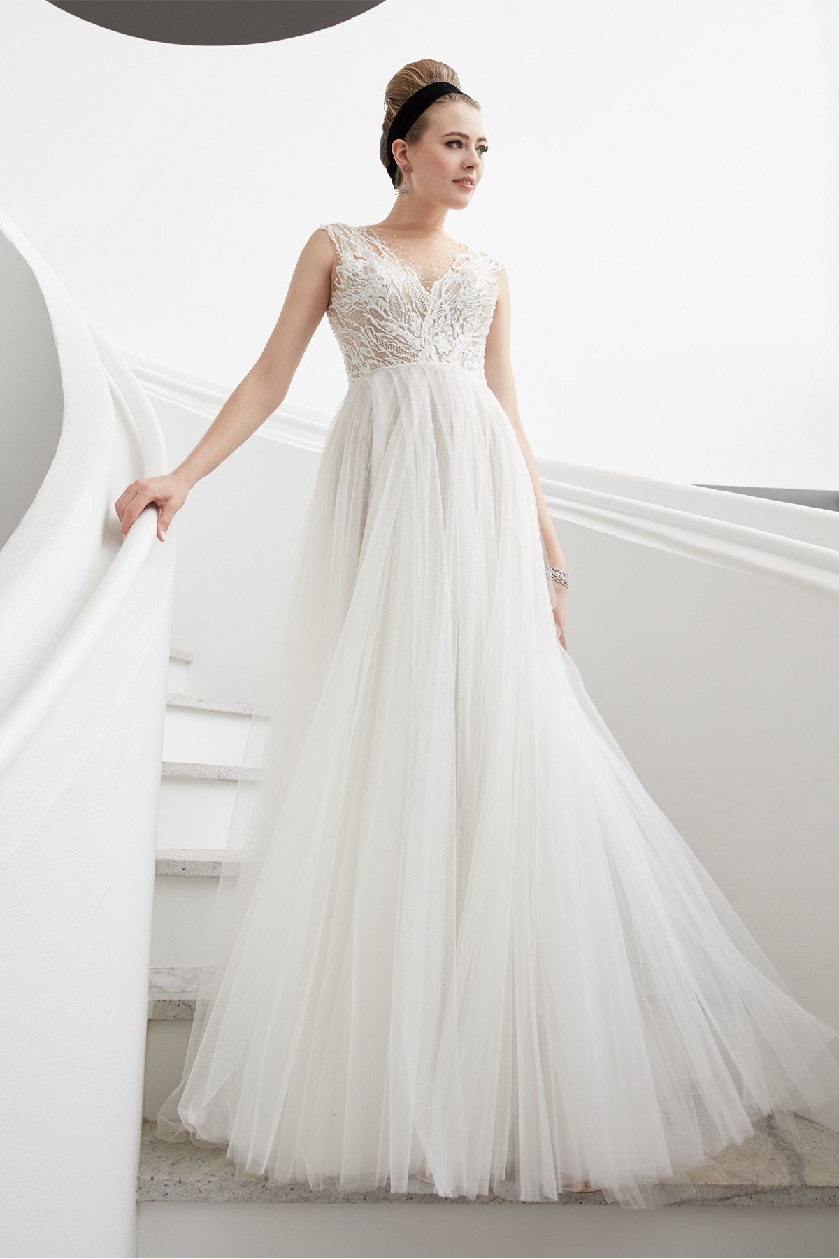 Model in bridal ballgown with tulle skirt and an embroidered illusion neckline