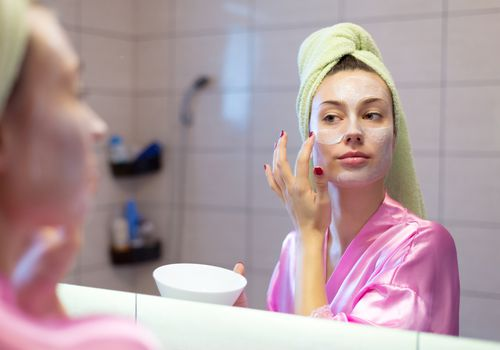Young woman putting facial mask on her face in front of the mirror