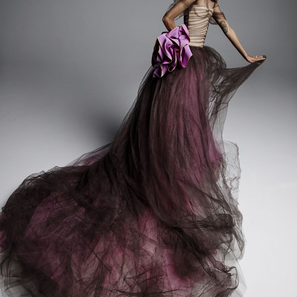 Model in purple and black tulle skirt with a nude bodice and light purple flower accents at the shoulder and waist